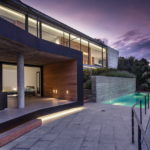 glass house with a swimming pool in the evening on the costa brava